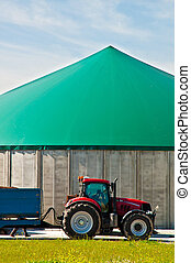 Red tractor and biogas - Red tractor and the tank of a...