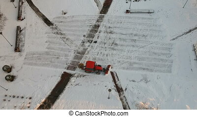 Red tractor cleaning removing snow from city square, aerial view