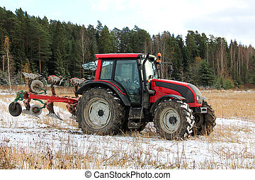 Red tractor and plough on field in early winter.
