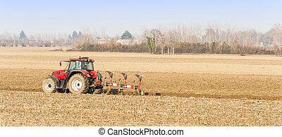 Red Tractor Plowing in Autumn.