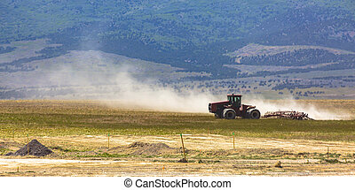 Red tractor with large wheels on a field in Utah