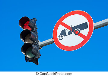 Red traffic light against a bright blue sky