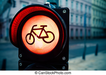 Red traffic light with bicycle sign with urban buildings in blurred background