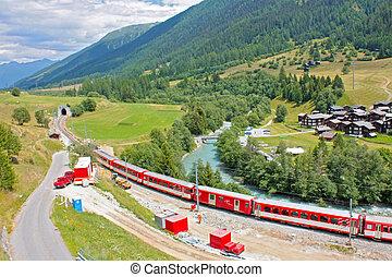 red train heading through high mountain valley in switzerland alps