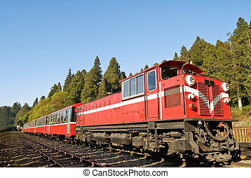 Red train under blue sky on railway forest in Alishan...