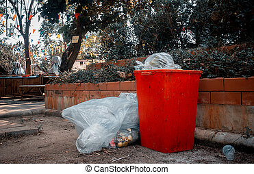 Red trash and trash bags in the park