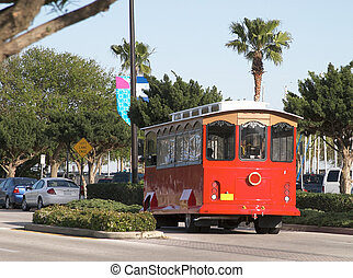 Red Trolly 2 - Red trolly car riding down palm tree lined...