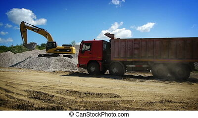 Red truck arrived to load gravel