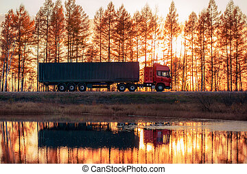 Red truck on a road at sunset. Focus on container