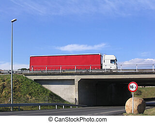 Red truck on the road crossing a bridge