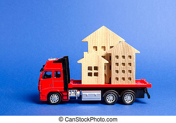 Red truck transports wooden houses. Concept of transportation and cargo shipping, moving company. Construction of new houses and objects. Industry. Logistics and supply. Move entire buildings.