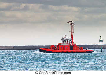 red tugboat navigates in port  waiting for a ship