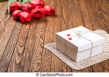 Red tulip bouquet and a gift box on a wooden table.