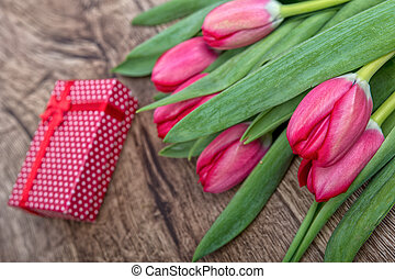Red tulips and gift on a wooden background