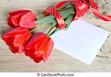 Red tulips bouquet & paper sheet on wooden background.
