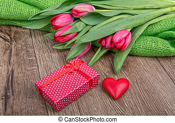 Red tulips, heart and gift on a wooden background
