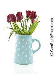 Red tulips in a blue spotted jug on white background