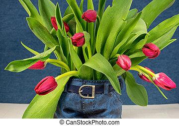 red tulips in blue jean pot