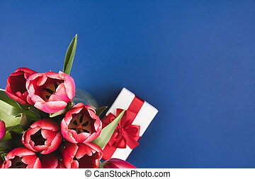 Red tulips on a blue background with a gift box