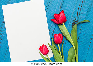 red tulips on a blue wooden board