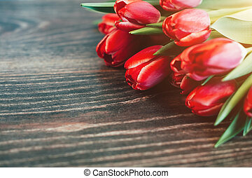 Red tulips on a dark wooden background