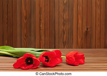 Red tulips on wooden background.