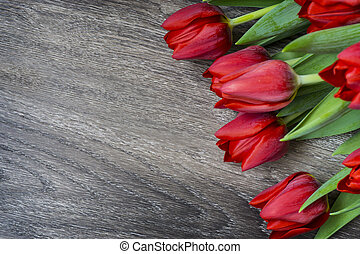Red tulips on wooden background with space for text