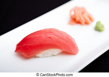 Red tuna sushi served on a plate with ginger and wasabi