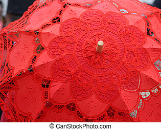 red umbrella hand-decorated with lace doilies