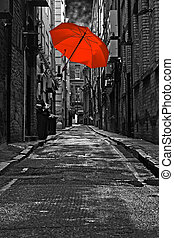 Red umbrella in a dark urban alleyway