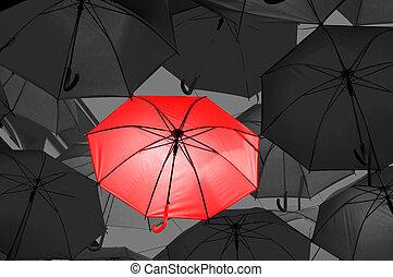 Red umbrella in black and white umbrellas