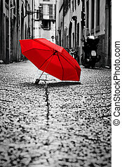 Red umbrella on cobblestone street in the old town. Wind and...