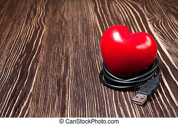 red valentine heart with usb cable on wooden brown surface