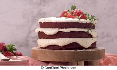 Red velvet cake with strawberries on kitchen counter top.