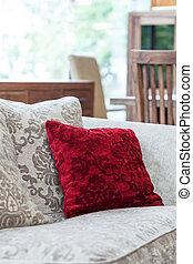Red velvet pillow - A closeup of an ecru sofa with a red...