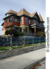 A red and gold victorian house with a blue picket fence