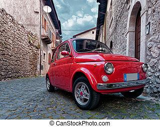 Red vintage city car parked in old village