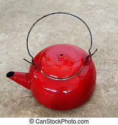 Red vintage metallic kettle on cement floor.