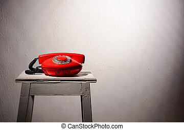 red vintage phone on a white stool