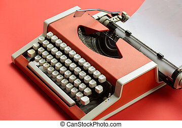Red vintage typewriter with white blank paper sheet on table