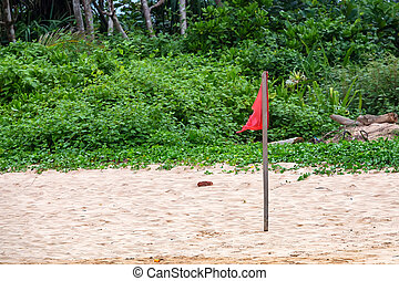 Red warning flag on beach showing that swimming is dangerous...