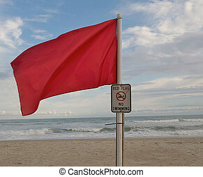 Red Warning flag on the beach.