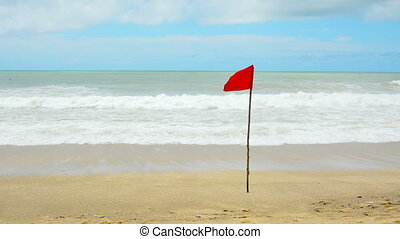 Red warning flag on the beach