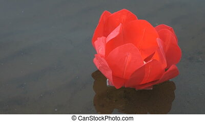 Red water lily with candle on the water - Festive ritual -...