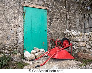 Red wheelbarrow lying on the floor in front of a green door