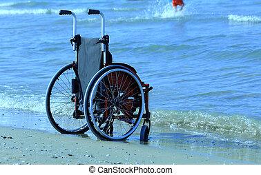 red wheelchair on sandy beach in summer