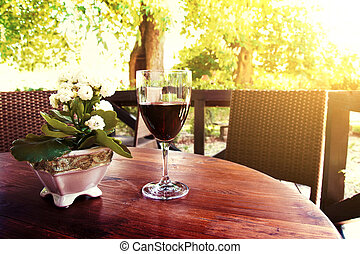 Red whine on the table in idyllic courtyard in restaurant.