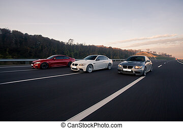 Red, white and silver sport sedan cars on the highway