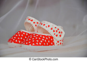 Red-white baby booties are on the crib