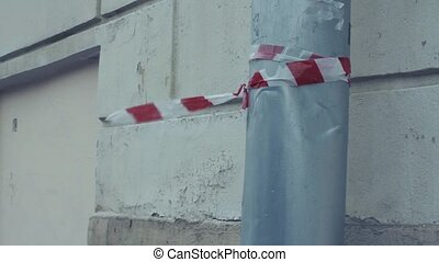 red white danger tape fluttering in the wind attached to a water pipe